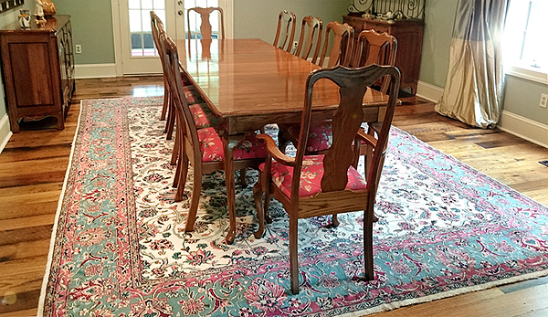 Dining room setting features antique carpet from Nejad